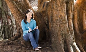 Woman writing diary by tree in park. Image shot 2009. Exact date unknown.