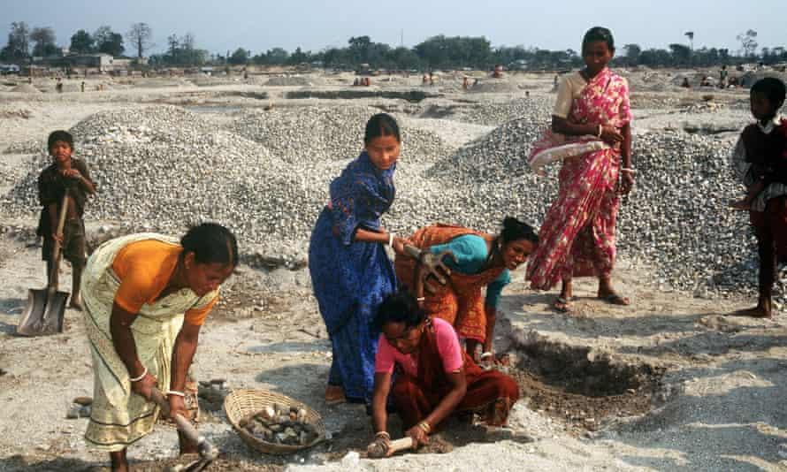 Indian women and children work as stone crushers.