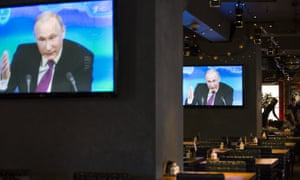 Russian president Vladimir Putin on TV screens in Moscow during a three-hour press conference.