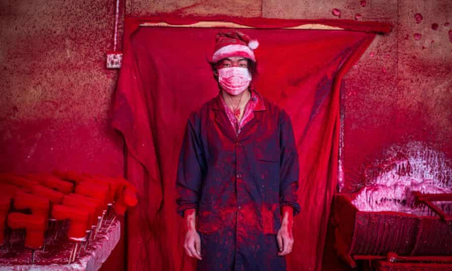 Santa's workshop … 19-year-old Wei works in a factory in Yiwu, China, coating polystyrene snowflakes with red powder.