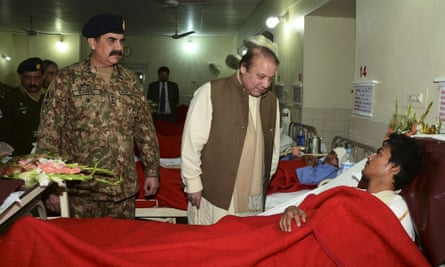Prime Minister Nawaz Sharif, talks to a student injured in Tuesday's school attack, accompanied by Army Chief General Raheel Sharif.