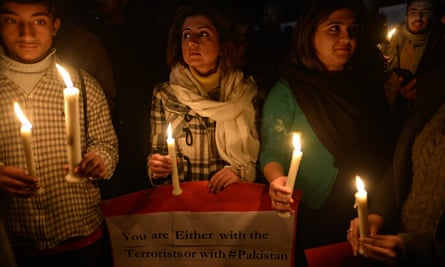 People light candles for school victims in front of the radical Red mosque in Islamabad