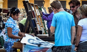 Tourists look at posters for sale in Havana on 18 December 2014.