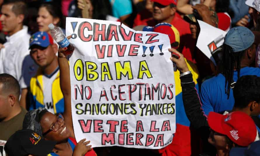 Supporters of President Nicolas Maduro hold a banner during a rally to reject US sanctions against Venezuela.