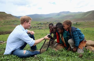 Britain's Prince Harry shows children a photograph he has taken on a camera during a visit to a herd boy night school constructed by Sentebale in Mokhotlong, Lesotho