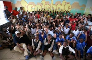Prince Harry poses with children during a visit to the Thuso Centre for children living with multiple disabilities in Bute-Bute