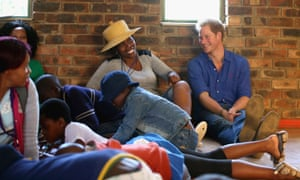 The prince sits next to a volunteer who was laughing at his singing during a visit to a Mamohato network club for children living with HIV at St Paul Centre in Maseru