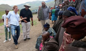 Prince Harry dances in front of herd boys with Prince Seeiso of Lesotho, wearing a hat, during a visit to a herd boy night school