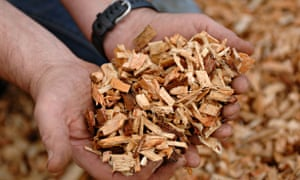 Using a woodchip machine to chop up logs for use in a biomass boiler
