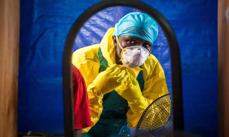 A healthcare worker dons protective gear before entering an Ebola treatment centre in Freetown, Sierra Leone.