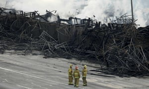 Firefighters stood on lanes of the 110 freeway near smoldering hot spots