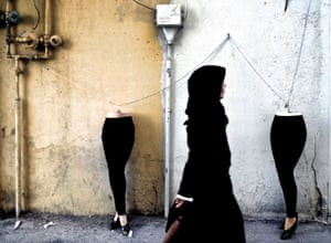 An Iranian woman walks past mannequins locked to a gas pipe in northern Tehran
