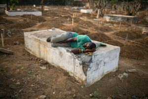 A grave digger sleeps near the graves of Ebola victims at a cemetery in Freetown, Sierra Leone.