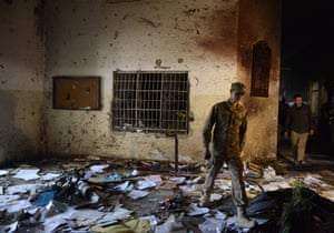A Pakistani soldier walks amidst the debris in an army-run school a day after an attack by Taliban militants in Peshawar