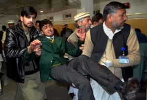 Pakistani volunteers carry a student injured in the shootout at a school under attack by Taliban gunmen, at a local hospital in Peshawar, Pakistan