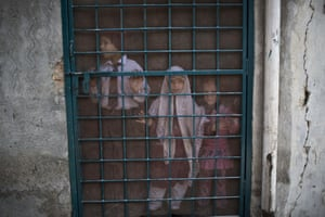 Pakistani schoolchildren look out the doorway of their school, before a special class about the victims killed in Tuesday's Taliban attack on a military-run school in Peshawar, at Ranrra school in Rawalpindi, Pakistan
