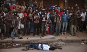 Bystanders stand around the body of a suspected Ebola victim lying in a street in the town of Koidu, Kono district in Eastern Sierra Leone