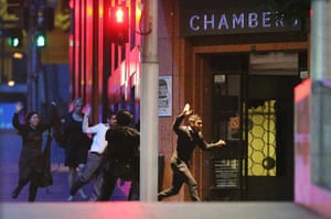 People run with their hands up from the Lindt Cafe during a hostage standoff on December  in Sydney, Australia.  Police stormed the Sydney cafe as a gunman has been holding hostages