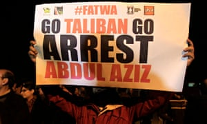 A man holds a sign during a protest near the Red Mosque in Islamabad