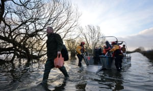 Residents disembark a boat after being transported from the cut-off village of Muchelney in Somerset