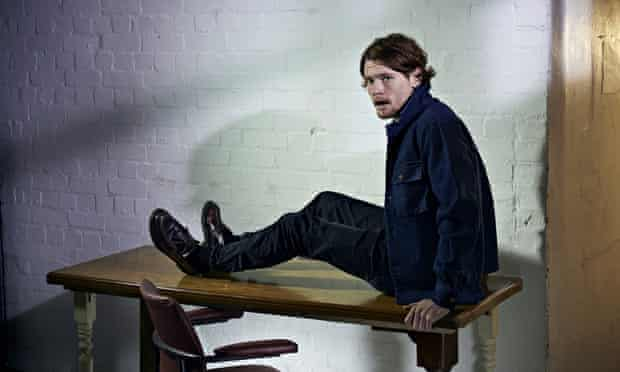 jack oconnell sitting on a table in a sparse room