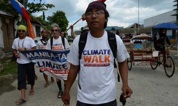 Philippine climate change envoy Naderev Sano (front R) walks with colleagues along the streets of Basey town, Western Samar on November 7, 2014, after reaching the town the night before as part of his 1,000-kilometre (660-mile) trek to Tacloban, a major city in the central Philippines that was among the worst hit when Super Typhoon Haiyan crashed in off the Pacific Ocean exactly one year ago. Sano will on November 8, reach ground zero of the strongest typhoon ever to hit land, completing an epic march he believes will help spur global warming action.