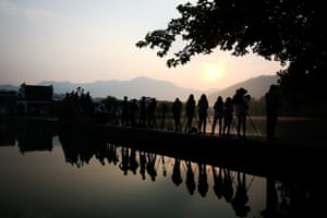 HUANGSHAN, CHINA - JUNE 12: Photographers take photos of sunrise on June 12, 2014 in the ancient Hongcun Village, China.