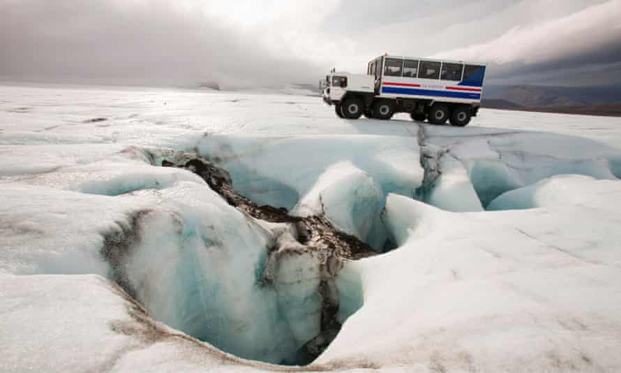 An ice explorer truck next to a sinkhole for meltwater – it's used to take tourists on to the Langjokull ice cap.