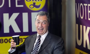 Nigel Farage laughs as he holds a coffee cup