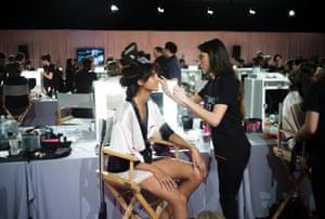 A makeup artist prepares a model for the catwalk