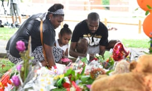 Members of the public lay flowers at a memorial in the park next the home of a multiple stabbing in the suburb of Manoora.