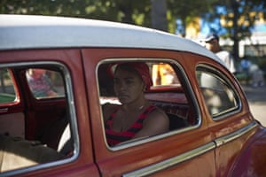A woman waits in a classic American car that's used as a shared taxi by commuters in Havana, Cuba