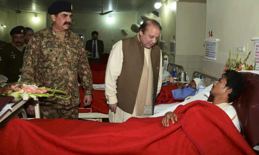 Prime minister Nawaz Sharif talks to a student injured in the massacre as army chief General Raheel Sharif looks on.