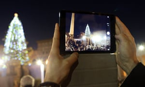 Visitors gather in the Vatican's St. Peter's Square to watch the switching on of the Christmas tree lights