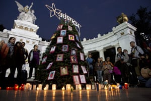 In Mexico City people decorate a Christmas tree decorated with pictures of the 43 students who have now been missing for more than two months and are now presumed dead after being attacked by police in southern Mexico