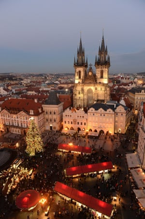 An illuminated christmas tree sits in the centre of the christmas market in Prague's Old Town Square