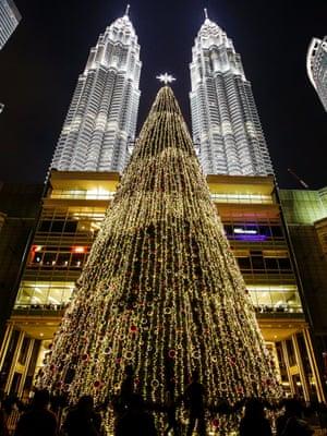 epa04523415 A Christmas tree stands against the Malaysian landmark Petronas Twin Towers in Kuala Lumpur, Malaysia