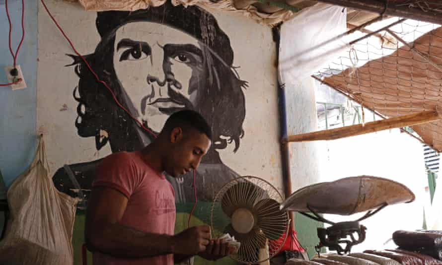 """A worker who sells beans counts money at a state-run market stall decorated with a mural of Cuban revolutionary hero Ernesto """"Che"""" Guevara in Havana."""