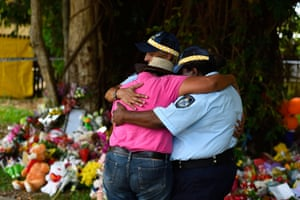 Cairns, Australia Mourners embrace near the home of a multiple stabbing in the suburb of Manoora. Eight children were found dead and a woman is in hospital with injuries