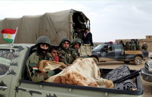 Sinun, Iraq Peshmerga fighters wrapped in a blanket, arrive to fight against Islamic State in Iraq