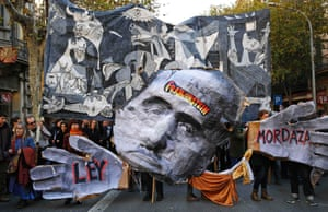 Barcelona, Spain Demonstrators hold a cut-out of former Spanish dictator Francisco Franco and a banner of Picasso's Guernica  to protest against Ley Mordaza bill which limits freedom of expression and gives more power to police