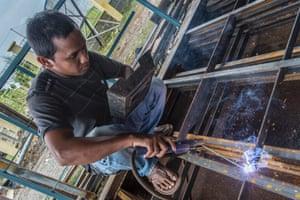 Welder Safriadi at work in Kuta Padang, Meulaboh