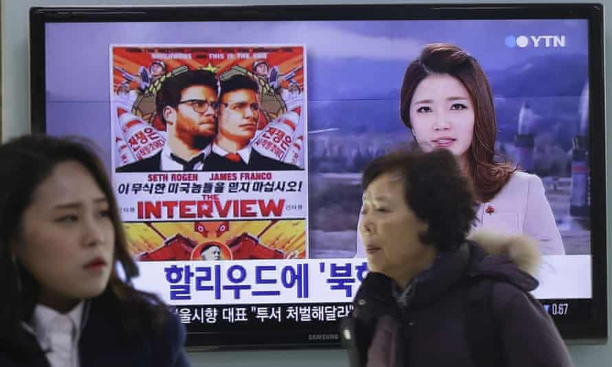 Commuters walk past a poster for The Interview shown on a news report in Seoul railway station, 22 December.