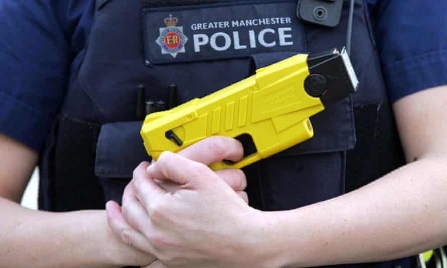 A member of Greater Manchester Police holding a Taser weapon
