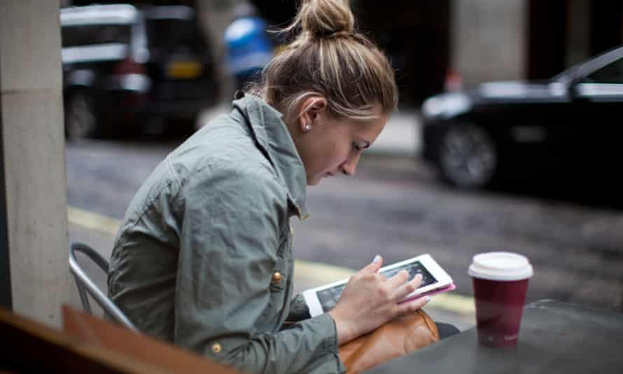 A woman uses her iPad on Oxford Street.