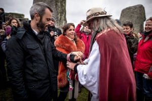 A couple take part in a handfasting ceremony inside the stone circle, a Pagan wedding ritual
