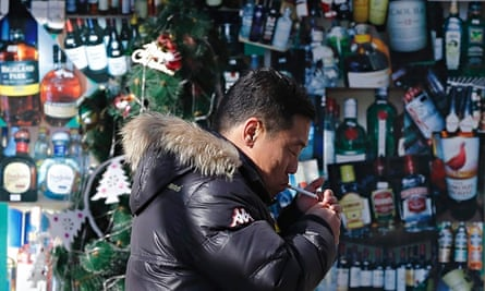 A Chinese man lights a cigarette