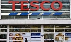 Woman walks past a Tesco supermarket