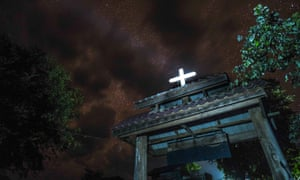 Cross reflects moonlight atop Christian church in Thailand.