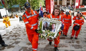 Volunteers carry away a photo tribute of Katrina Dawson and Tori Johnson at Martin Place on December 23, 2014 in Sydney, Australia.